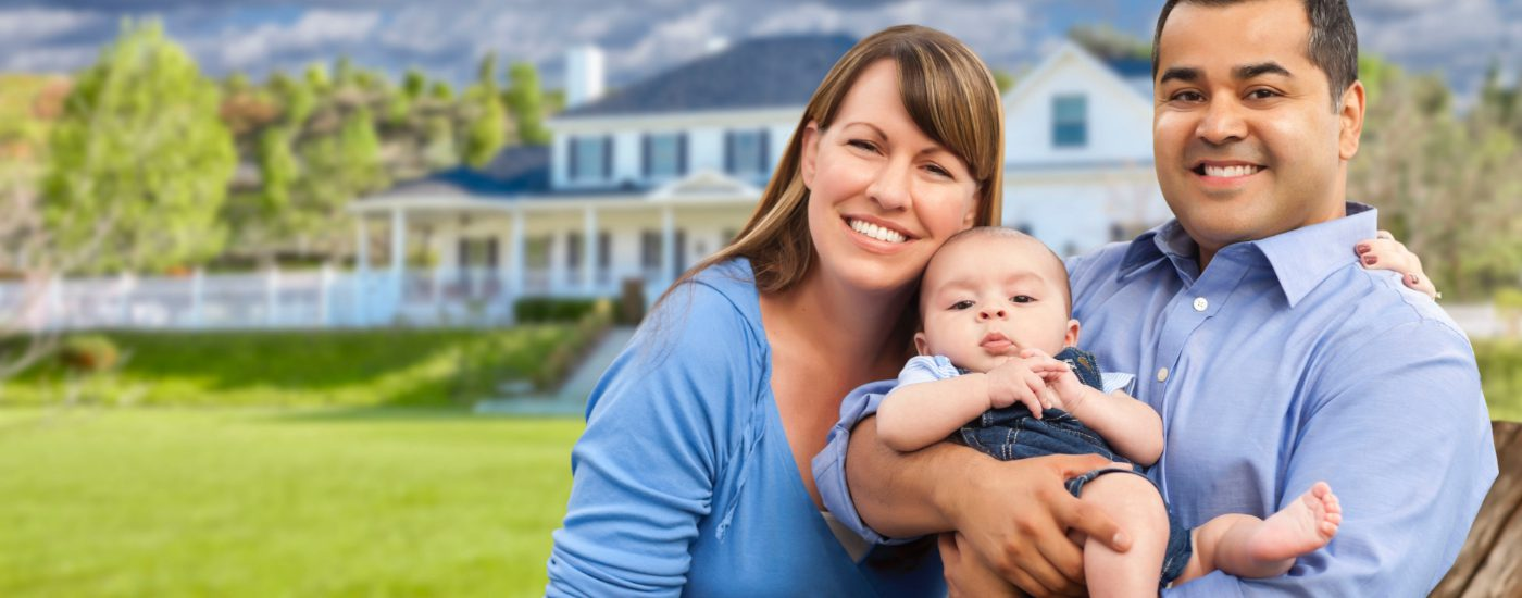 Smiling couple holding baby at family home